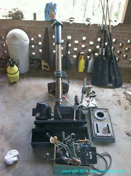 The drill press in the carport, with stuff